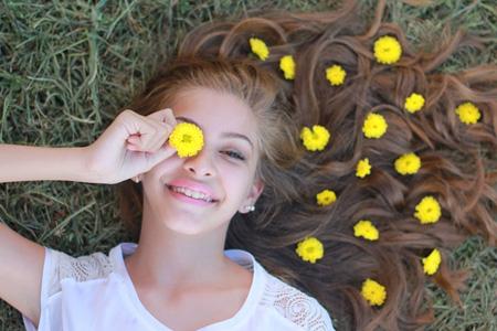 躺在草地上拿鲜花的女孩